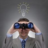 Inspiration concept businessman looking through binoculars in front of a light bulb drawing on blackboard metaphor for good idea