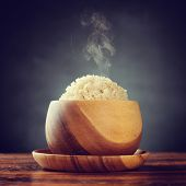 Cooked organic basmati brown rice in wooden bowl with hot steam smoke on dining table. Low light set