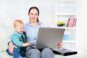 Young business woman with laptop and her baby boy