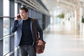 Urban business man talking on smart phone traveling walking inside in airport. Casual young business