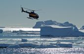 Helicopter Over Antarctic Icebergs