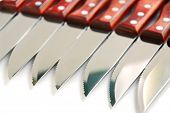 Steak knives in a row on white background