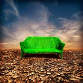Ecology And Global Warming Concept. Grassy Sofa Standing at drought cracked desert landscape