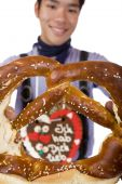 Man Holding Oktoberfest Pretzel In Camera