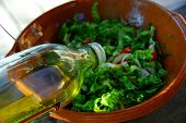 Olive oil being poured into garden salad for salad dressing