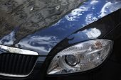 stock photo of dimples  - dented damaged surface of a dark car and its headlight lamp - JPG