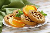 mini dessert tarts with orange on wooden table