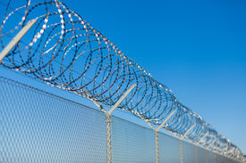 picture of safety barrier  - Coiled razor wire with its sharp steel barbs on top of a wire mesh perimeter fence ensuring safety and security preventing access or the escape of prisoners blue sky background - JPG
