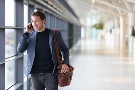 pic of jacket  - Urban business man talking on smart phone traveling walking inside in airport - JPG