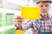 image of dungarees  - Farmer in checked shirt and dungarees holding a sign at supermarket - JPG
