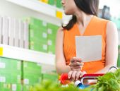 Woman At Supermarket With Shopping List
