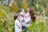 Young Beautiful Woman Playing With Her Son And Daughter In A Colorful Field