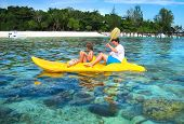 Father And Son Kayaking Next To A Tropical Coral Island