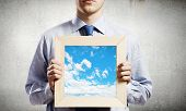 Young smiling businessman holding wooden frame with sky picture