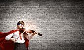Cute girl of school in superhero costume playing violin