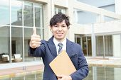 Smiling businessman with thumbs up