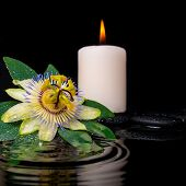 Spa Setting Of Passiflora Flower, Green Leaf With Drop And Candles On Zen Stones In Ripple Reflectio