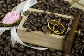 Wedding rings in a drawer filled with coffee beans and flower