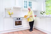 Happy Grandmother Baking A Pie In A White Kitchen
