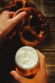 image of pretzels  - man holding beer and pretzel on a dark wood background - JPG