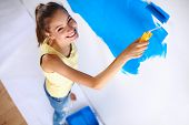 Happy beautiful young woman doing wall painting, standing on la