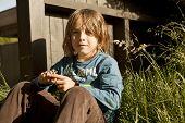 Boy Sitting In The Garden