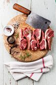 Raw Fresh Lamb Ribs With Salt, Pepper And Cumin And Meat Cleaver On Wooden Cutting Board On Blue Bac