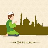 Muslim boy praying (Namaz, Islamic Prayer) in front of mosque on beige background for Eid-Ul-Adha festival celebrations.