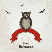 Scary owl sitting on red ribbon with flying bats on grungy grey background for Happy Halloween celeb