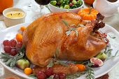 foto of harvest  - Roasted turkey on a server tray garnished with fresh figs grape kumquat and herbs on fall harvest table. Red wine side dishes pie and gravy. Decoraded with mini pumpkins candels and flowers.