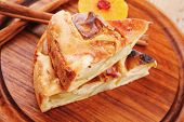 baked food: apple pie on wooden table served with lemon and cinnamon sticks