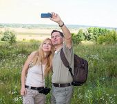 stock photo of two women taking cell phone  - Woman and man hiker with backpacks taking self picture photo with smart phone camera - JPG