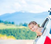 Happy girl travel by car in the mountains. Summer vacation concept