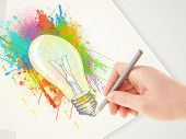 Hand drawing on a plain paper a colorful splatter lightbulb
