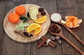 Mulled wine ingredients of citrus fruit and spices over oak background.