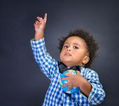 Happy preschooler discovering world, african boy with raised up hand understand something and holding globe in another,  geography lesson, back to school concept