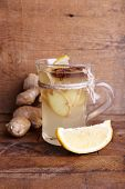 Cup of ginger drink with lemon on wooden table on wooden wall background