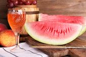Composition of ripe watermelon, fruits, pink wine in glass and wooden barrel on rustic wooden backgr