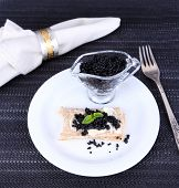 Slice of bread with butter and black caviar on plate on fabric background