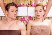 Beautiful couple lying in a spa salon enjoying head massage together.