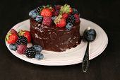 Tasty chocolate cake with different berries on wooden table, on dark background
