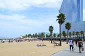 BARCELONA - AUGUST 9: Tourists enjoy the sunny weather and relaxing on the Barceloneta beach on 9 August 2014 in Barcelona, Spain. This is one of the best beaches in the world.