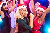 Happy people in Santa hats dancing at party