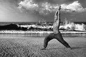 picture of virabhadrasana  - Young man doing yoga and meditating in warrior pose at sea beach - JPG