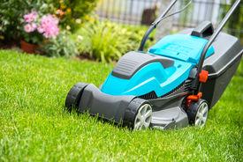 stock photo of grass-cutter  - Lawn mower on a green meadow - JPG