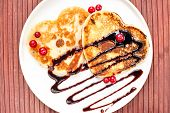 picture of dessert plate  - Heart shaped pancakes with chocolate sauce and red cranberries on white porcelain plate - JPG