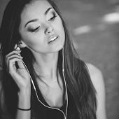 Beautiful girl listening to music in the park in the summer.