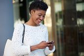 Happy Young Woman Walking In The City Sending Text Message