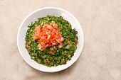 Plate of traditional Arabic salad tabbouleh on a rustic table