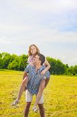 Smiling Caucasian Man Giving Woman Piggyback Ride Outdoors. Youth Lifestyle, Happiness, Love, Dating